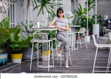 Portrait of a confident, fashionable and attractive middle-aged Chinese Asian woman sitting in a trendy cafe during the day. She is wearing a pair of sunglasses as she enjoys the sun outdoors.