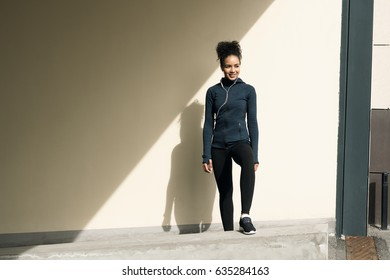Portrait of confident female athlete leaning standing at wall