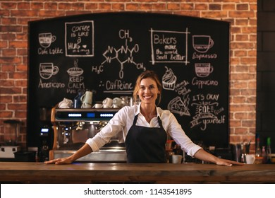 Portrait of confident female barista standing behind counter. Woman cafe owner in apron looking at camera and smiling.