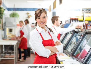 Portrait of confident female butcher standing arms crossed with colleagues in background