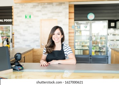 Portrait of confident female cashier at checkout counter in supermarket