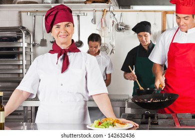 Portrait of confident female chef with colleagues cooking in commercial kitchen