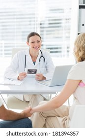 Portrait of confident female doctor with expectant couple sitting at desk in clinic