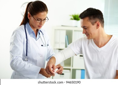 Portrait of confident female doctor giving first aid to male patient in hospital