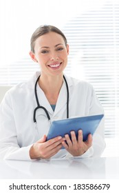 Portrait of confident female doctor holding digital tablet while sitting at desk in clinic
