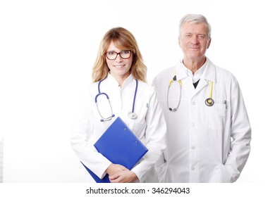 Portrait of confident female doctor holding in her hand a clipboard while standing with senior specialist doctor at white background.