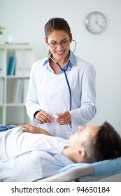 Portrait of confident female doctor looking at patient during medical treatment in hospital