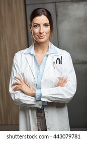 Portrait of confident female doctor standing in lab coat, smiling, looking at camera.