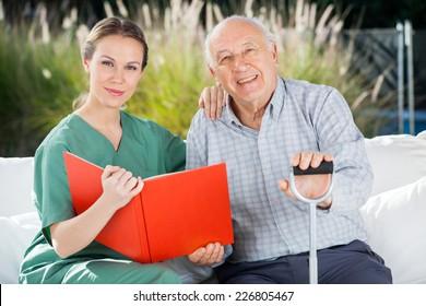 Portrait of confident female nurse and senior man with book at nursing home