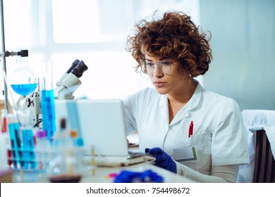 Portrait of confident female scientist working on laptop in chemical laboratory