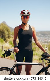 Portrait of confident female triathlete standing with her bicycle on country road. Fitness woman in sports wear standing with her bike. Female cyclist practicing for triathlon.