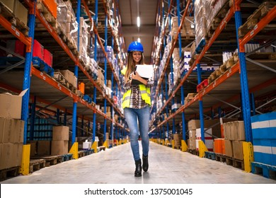 Portrait of confident female worker walking through distribution warehouse. Smiling woman holding checklist. Manager controlling distribution.