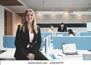 Portrait of confident fifty years old female manager working in modern office. Mature blond business woman smiling at work in coworking space, sitting on desk.