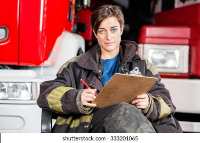 Portrait of confident firewoman holding clipboard while sitting against trucks at fire station