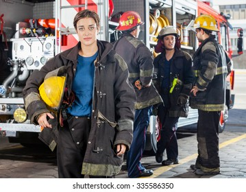 Portrait of confident firewoman holding helmet while male colleagues discussing by truck in background at fire station