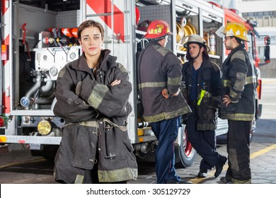 Portrait of confident firewoman with male colleagues discussing by truck in background at fire station