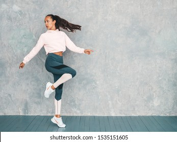 Portrait of confident fitness woman in sports clothing looking confident.Young female wearing sportswear. Beautiful model with perfect tanned body.Female jumping in studio near gray wall