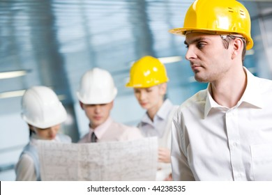 Portrait of confident foreman in helmet in working environment