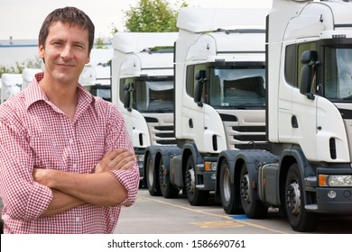 Portrait of confident freight transportation truck driver owner near trucks parked in a row
