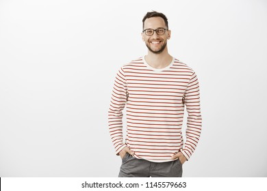 Portrait of confident friendly Caucasian employer in black glasses and striped pullover, holding hands in pockets and smiling cheerfully while greeting employees in office during casual meeting