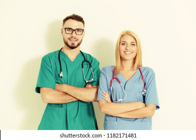 Portrait of confident GP doctor and surgical doctor with arms crossed on white background.