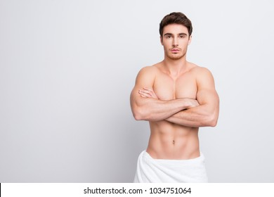 Portrait of confident handsome attractive sexual with naked nude shirtless torso clean clear flawless ideal skin with white towel on hips isolated on gray background