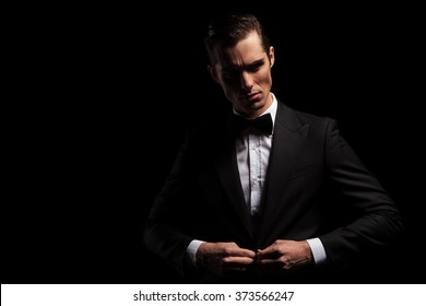 portrait of confident handsome man in black suit with bowtie posing in dark studio background while closing his jacket