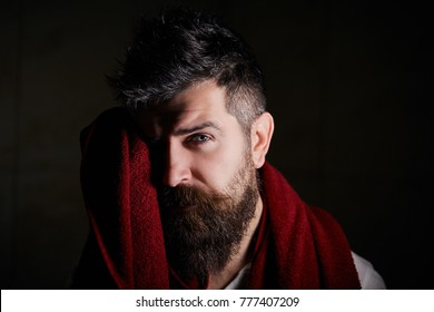 Portrait of confident handsome sexual serious bearded man with trendy hairdo, using a red towel to wipe himself after wash and taking a morning shower, isolated on dark background