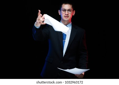 Portrait of confident handsome stylish businessman holding papers in his hands on black background