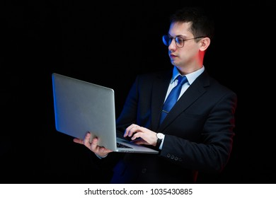 Portrait of confident handsome stylish businessman holding laptop in his hands on black background