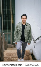 Portrait of a confident, handsome and stylish Chinese Asian man in the city. He is climbing steps and holding onto his smartphone and is wearing a comfortable and stylish casual outfit.