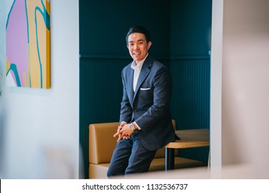 Portrait of a confident, handsome young Chinese Asian professional man wearing a suit and leaning against a table in his office. He is athletic and muscular and smiling as he smiles for his head shot.