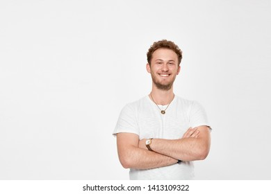 Portrait of a confident handsome young man with a beard infront of white bakground. Model in a white t-shirt smiles to the camera and keeps arms crossed.