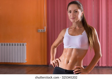 Portrait of Confident Healthy Brunette Woman Wearing Performance Wear Standing in Dance Studio with Hands on Hips and Smiling at Camera - Woman in Colorful Studio with Copy Space