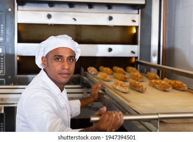 Portrait of confident Hispanic man engaged in breadmaking, taking baked baguettes out of industrial oven in bakeshop