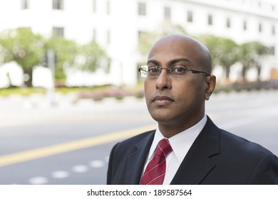 Portrait of a confident Indian Business man standing in modern city. Business man looking at camera.