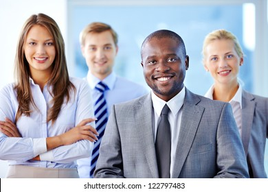 Portrait of confident leader looking at camera with three partners behind
