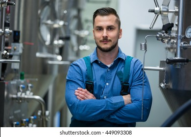 Portrait of confident maintained worker standing with arms crossed at brewery