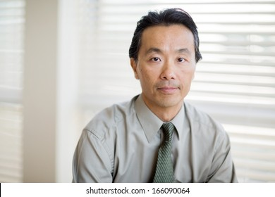 Portrait of confident male cancer specialist in shirt and tie at clinic