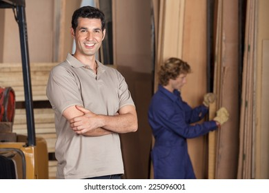 Portrait of confident male carpenter with arms crossed standing in workshop
