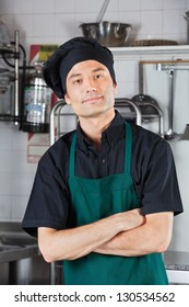 Portrait of confident male chef with arms crossed in restaurant kitchen