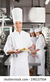 Portrait of confident male chef presenting dish with colleagues standing in background at commercial kitchen