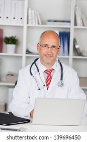Portrait of confident male doctor with laptop at office desk