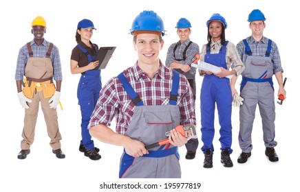 Portrait of confident male engineer holding tool with team against white background