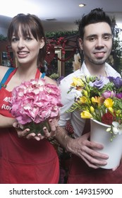 Portrait of confident male and female florists holding flower vases in shop
