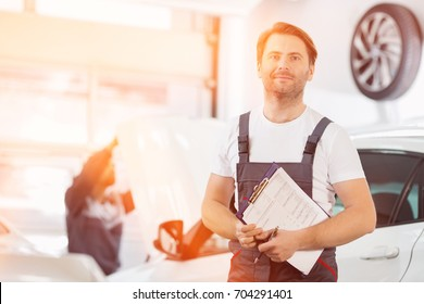 Portrait of confident male maintenance engineer with clipboard in car repair shop