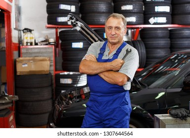 Portrait of confident male mechanician posing near car at auto service