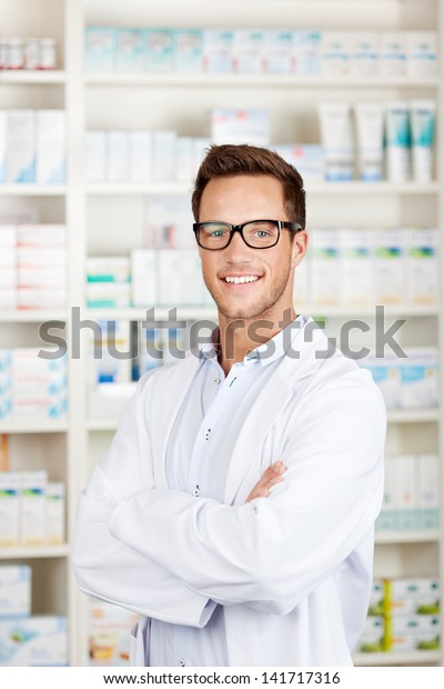 Portrait of a confident male pharmacist smiling in front of medicines at drugstore
