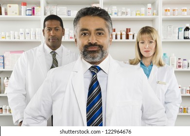 Portrait of a confident male pharmacist standing with two colleagues at workplace