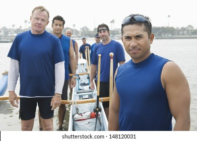 Portrait of confident male rower with multiethnic outrigger canoeing team